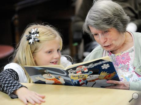 Central Columbia third-grade student Maggie Campbell and an Orangeville Health and Rehabilitation Center resident share a book on Frosty the Snowman Friday afternoon.