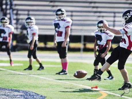 Bloom White B Team player Jordan Gallagher, right, kicks off at the start of Sunday afternoon's BYFL game against the Locker Room Redskins B Team at Crispin Field in Berwick.