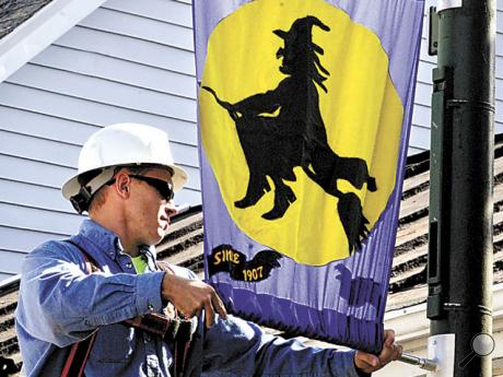 Catawissa electric department worker Brandon Auten hangs a witch banner, on Wednesday, along Main Street in Catawissa in preparation for the 109th annual Catawissa Halloween Parade.