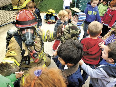 Dressed in turnout gear, Danville firefighter Tyler Patterson, a lieutenant with Goodwill, gives high-fives to children at the Danville Child Development Center's Wall Street facility during a Fire Prevention Week visit on Tuesday.