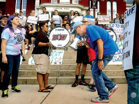 Bloomsburg University history prof Bill Hudon leads a chant with a bullhorn while stepping to the beat of drummers during picketing with fellow faculty members in front of Carver Hall on campus on Wednesday. Behind him students rally in support of the striking faculty.