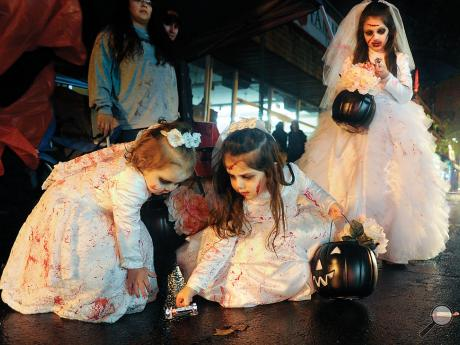 Zombie brides, from left, November Maurer, 1, Savannah Maurer, 3, and Cheyenne Maurer, 8, pick up candy while standing along Mill Street watching the Danville Halloween Parade Thursday night.