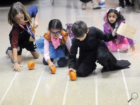 From left, Thea Sommer, Jiya Khara, John Friedenberg and Saanvi Khara roll pumpkins down a track Wednesday night, one of the games at  St. Joseph School's Trick-or-Treat Night.