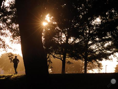 A runner heads along Fort McClure Blvd. as the sun sets Wednesday evening in Bloomsburg.