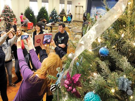 The team from Northeast Ear, Nose and Throat takes pictures and selfies with their Christmas tree after finishing decorating Sunday afternoon at the Caldwell Consistory in Bloomsburg for TreeFest. TreeFest opens Friday at 5 p.m. and will have 133 decorated trees on display along with handmade crafts for sale, live entertainment and a Chinese auction.