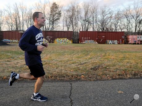 Doug Brown runs along East First Street in Mifflinville Monday afternoon as he takes advantage of the warm weather, putting in seven miles, while a train heads north in the background.