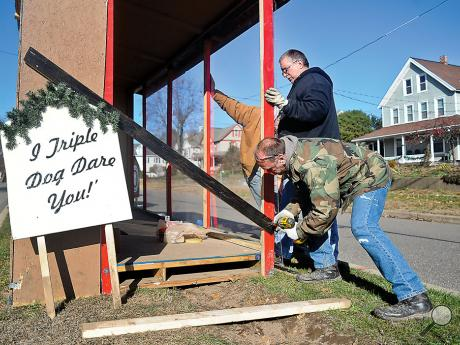 Clair Davis, Bloomsburg, back, watches as John Gurns, Berwick, front, removes a piece of wood from the Christmas Story area of the Wise Potato Chips plot on Market Street in Berwick on Sunday afternoon in preparation for the opening of the Christmas Boulevard on Friday at 6 p.m.