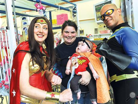 Superheroes Wonder Woman, left,  and Black Knight pose with Winter Martz, eight months and her mother Phylicia Martz in the Pediatric Intensive Care Unit at the Janet Weis Children's Hospital Tuesday afternoon.