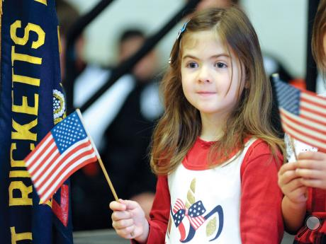 Benton Elementary's Hannah Getz smiles as she waves her flag during the annual Veteran's Day program at the Benton Elementary school Monday morning.