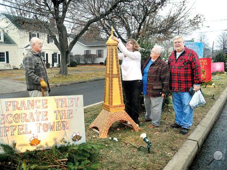 "Volunteers, from left, Frank Campbell, Kimberly Young, Doreen Campbell and Rick Wynings work on the ""Christmas Around the World"" plot on Christmas Boulevard along Market Street in Berwick on Thursday."