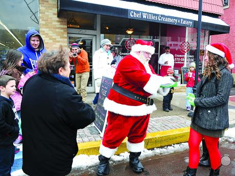 Santa and his elves hand out candy canes to families lined up on Mill Street after is arriving in Danville for the holiday season. Santa's cottage, located between the borough municipal building and Beiter's Department store, will be open from 5 p.m. to 7 p.m. Fridays and noon until 3 p.m. on Saturdays through Dec. 21.
