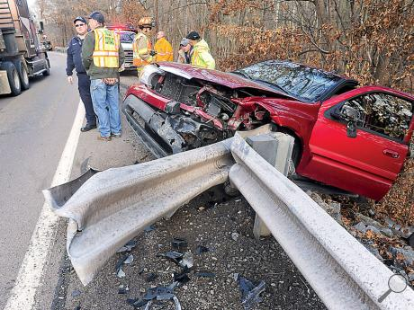 Rescue crews stand at the scene of this one-vehicle crash along Route 487 in Fishing Creek Township Thursday afternoon. Nancy Colprit, 76, Orangeville, crashed her Buick Rainier after reaching for her purse while traveling south towards Orangeville.