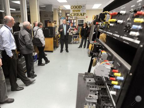 Columbia-Montour Vo-Tech Administrative Director David Bacher, center, stands in the middle of the Electrical Occupations shop area while explaining the hands on work the students do the vocational program during a tour of the shops Wednesday evening.