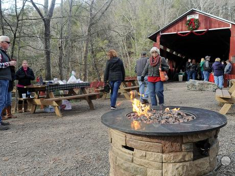 A fire pit burns outside of the Josiah Hess Covered Bridge Sunday afternoon for visitors to warm up by during the Columbia County Covered Bridge Association's Christmas on the Bridges.