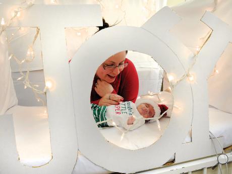 Amber Johnson of Williamsport holds the hand of her son Cooper Johnson, who was born on Nov. 18, while doing a Christmas photo shoot in the NICU at Geisinger'sJanet Weis Children's Hospital Wednesday evening.