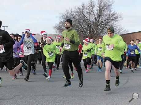 Participants in the first Santa Claus 5k Run/Walk take off at the start of the race on Sunday afternoon at Millville Elementary School. The run/walk benefited the Millville Boys Basketball Team as well as the Sawyer Peterman Scholarship Fund.