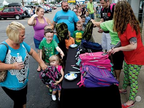Michelle Mowery, at left, helps Hannah, 3, and Derek Mountz, 8, pick out backpacks during a backpack giveaway at The Cellular Connection, a Verizon retailer, Sunday afternoon in Berwick. Both children selected camouflage backpacks. The store gave away more than 200 backpacks to area children at the annual charity event.
