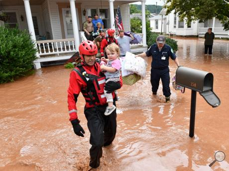 Members of the Columbia/Montour SWAT team and a crew from a Montour water rescue team remove the Jason Simpkins family from their home at 250 Colley Street in Benton, Monday as flood water from Fishing Creek fills the borough.