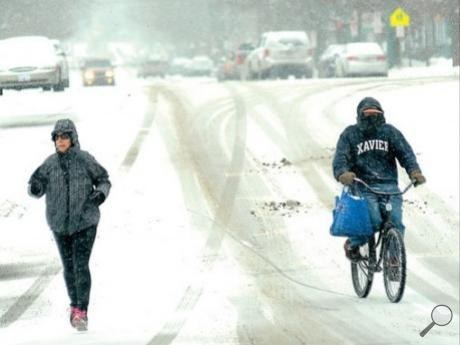 Greg Badger, Bloomsburg, passes a jogger on Market Street in Bloomsburg while peddling home after running some errands and helping people during a stormy Tuesday afternoon.