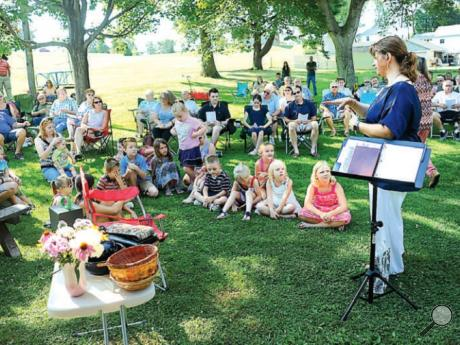 The Rev. Jenn Parks-Snyder of Lightstreet United Methodist Church addresses the children of the congregation after opening the annual Sunday morning service in Lightstreet Park.