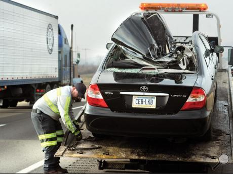 Joe Stigerwalt, from West End Towing, secures a damaged Toyota to a flatbed truck Wednesday morning.
