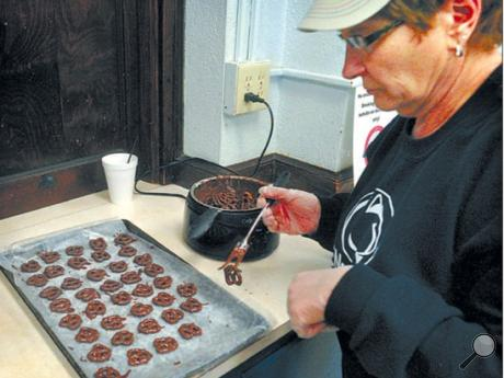 <p>First Presbyterian Church Deacon Janice Moskaluk, above right, dips pretzels in chocolate in the church kitchen. The deacons are holding an Easter egg, chocolate-covered pretzel and lollipop fundraiser. They're taking orders and making weekly deliveries up to March 20. For more information, call the church at 570-759-9461.</p>