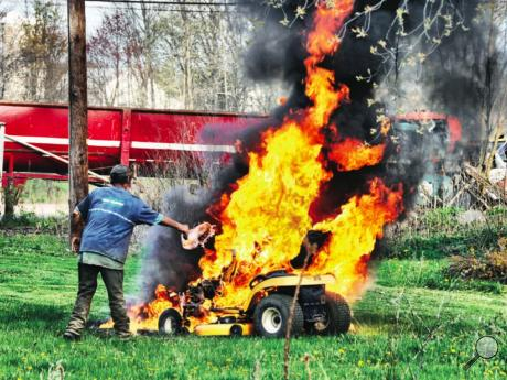 A Millville man dumps water from a coffee pot on a blazing lawn tractor Sunday evening. The tractor caught fire as owner Joe Temple was mowing grass around 6 p.m. at his 105 Blackbird Road property, a fire official said. Temple said the Cub Cadet backfired and flames shot out from under the hood, according to Rod Eves, Millville assistant fire chief. Temple immediately jumped off the mower and wasn't hurt, and the fire was in the middle of the lawn so nothing else was damaged, Eves said. Temple tried to fig