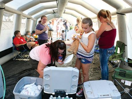 Julie Charlton, Danville, left and her daughter, Clare, 11, take free bottles of water after stepping into the Danville Fire Department's rehab tent Sunday afternoon near the fair office. The tent gave fairgoers a chance to cool off in a shaded tent with misting fans blowing. Danville Fire Department plans to be at the fair today and as needed the rest of the week. There are other cooling stations set up around the fairgrounds.