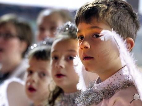 Derek McCabe, right, plays the part of an angel with other members of his first grade, in background, Isaac Pellegrini and Nina Nowak during the St. Mary's Catholic Church CCD program's annual Christmas pageant.