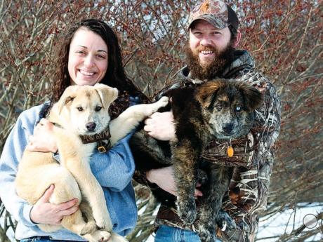 Sa M Ma GNI , left, holds Ruger while boyfriend Ben Francioni poses with Riddick earlier this month. The couple recently brought the adopted 15-week-old pups to their Fishing Creek Township home.