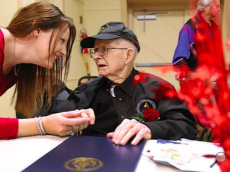 Donna Schronick of Port Byron, Illinois, at left in photo at right above, leans over to talk with her grandfather, Roy Kilpatrick, while attending his 100th birthday party at the Bloomsburg American Legion on Saturday.