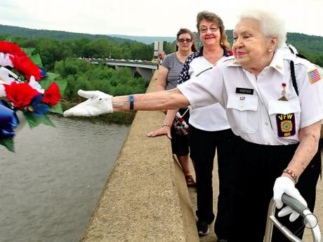 Betty Krepich tosses a flower wreath from the Berwick-Nescopeck bridge into the Susquehanna River during a brief stop by the participants in the Memorial Day parade Sunday. Behind her is Lois Kershner and in the back is Deb Podlinsek, who both also dropped flower wreaths from the bridge.