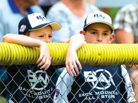 Peyton Vanvalkenburgh and Dominick Zangardi, both 10, of Dallas watch the Back Mountain All-Stars play over the outfield fence during the Major Division state Little League Baseball tournament game at Ber-Vaughn Park on Sunday afternoon.