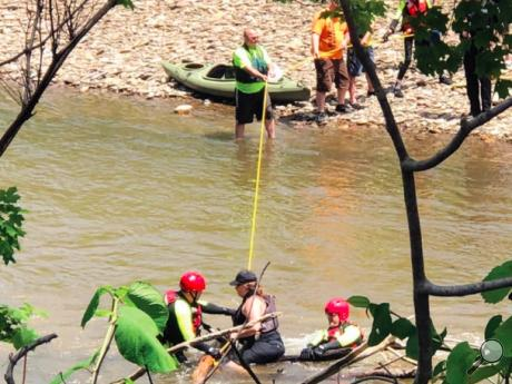 Bloomsburg Deputy Fire Chief John Mahon, left, reassures a stranded kayaker on Fishing Creek as Fire Chief Scott McBride, right, waits behind her to help her to safety.