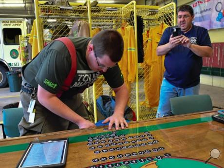 Catawissa firefighter Brandon Richendrfer puts the tag numbers into a bucket while Louie Richendrfer posts the fire department's raffle to Facebook live on a recent Friday night. The members had just returned from an accident to do the drawing. Online raffles are helping area fire companies make up for canceled fundraisers.