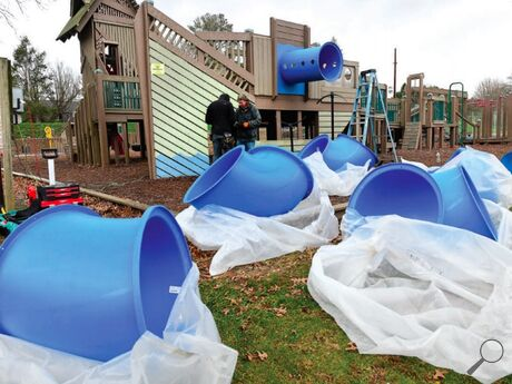 Elliot Wells and Mitchell Wright of Play By Design replace the slide on the south side of Kidsburg in Bloomsburg Town Park Tuesday morning. The company plans to have the work done by the end of the week.