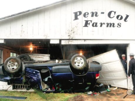 A Subaru Forester rests upside down inside a Pen-Col Farms barn along Route 254. At right, owner Dennis Wolff, left, talks to state police.