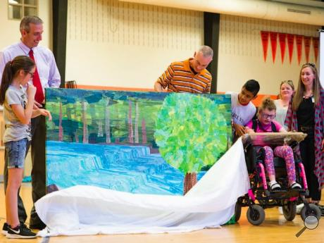 During the Wheels of Friendship presentation, L.R. Appleman Elementary fifth-graders and faculty help McKenzie Clink, 11, third from right, unveil the painting she and her classmates worked on at the Benton school. Clink used the wheels of her wheelchair and her hands to paint the Benton Dam with the fifth-grade class.