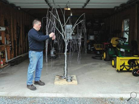 Mark Golomb, 61, wraps wire to create the branches of a willow tree in his garage on Wedgetown Road near Buckhorn. He is making the piece for the Tamaqua Community Art Center. It will be delivered by the end of this month.