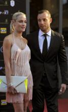 In this Nov. 4, 2012 photo, South African Olympic athlete Oscar Pistorius and Reeva Steenkamp, believed to be his girlfriend, at an awards ceremony, in Johannesburg, South Africa. Olympic athlete Oscar Pistorius was taken into custody and was expected to appear in court Thursday, Feb. 14, 2013, after a 30-year-old woman who was believed to be his girlfriend was shot dead at his home in South Africa's capital, Pretoria.