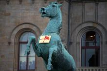 A golden Leibniz cookie hangs from a horse's neck in front of the Leibniz University in Hannover, Germany, Tuesday.