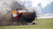 A stunt plane crashes during a wing walker's performance at the Vectren Air Show, Saturday, June 22, 2013, in Dayton, Ohio. The crash killed the pilot and the wing walker instantly, authorities said. (AP Photo/Thanh V Tran)