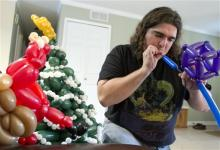 n this Nov. 12, 2012, photo, Tim Thurmond, works on a sculpture of Christmas-themed balloons in Brighton, Mich. (AP Photo/Livingston County Daily Press & Argus, Gillis Benedict)