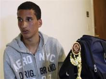 Salah Eddin Barhoum sits in his apartment in Revere, Mass., Thursday, April 18, 2013, with one of the trophies he won in an athletic competition, and the bag he was carrying on Monday near the finish line of the Boston Marathon. The 17-year-old from Morocco, whose photograph appeared on the front page of the New York Post in connection with the Boston Marathon bombings, told The Associated Press he has been scared to go outside because he worries people will blame him for Monday's attack. (AP Photo