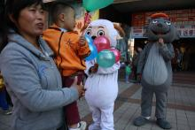 "In this photo taken Sunday, Oct. 2, 2011, a woman and child gather near mascots of characters from the cartoon ""Pleasant Goat and Big Big Wolf"" on a street in Beijing, China. (AP Photo/Ng Han Guan)"