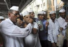 Dabbawalas, or lunchbox delivery men, pass out sweets in celebration of the birth of the Prince of Cambridge, the son of Britain's Prince William and Kate, Duchess of Cambridge, at a railway platform in Mumbai, India, Tuesday. (AP Photo/Rafiq Maqbool)