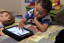 Frankie Thevenot, 3, plays with an iPad in his bedroom at his home in Metairie, La. As of Wednesday, Aug. 7, 2013, the Campaign for a Commercial-Free Childhood is urging federal investigators to examine the marketing practices of Fisher-Price's and Open Solution's mobile apps. It's the campaign's first complaint against the mobile app industry as part of its broader push to hold accountable businesses that market technology to very young children and their parents. (AP Photo/Gerald Herbert, File)