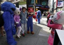 A man has his photo taken by a Hello Kitty character, right, as he poses with Cookie Monster, another Hello Kitty and Super Mario characters, in New York's Times Square, Tuesday, April 9, 2013. A string of arrests in the last few months has brought unwelcome attention to the growing number of people, mostly poor immigrants, who make a living by donning character outfits, roaming Times Square and charging tourists a few dollars to pose with them in photos. (AP Photo/Richard Drew)