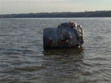 a giant head made of Styrofoam and fiberglass is seen floating in the Hudson River in Poughkeepsie, N.Y. Officials at the college in say their crew team was practicing earlier this week when the coach spotted a large object floating near the river's west bank. He hooked a rope to it and towed it to the team's dock on the east bank. (AP Photo/Marist College, Matthew Lavin)