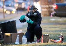 Rebecca Patrick, a forensic science with the State Police Clandestine Lab, looks through the items which team member removed from a home at 225 East Sixth Street in Bloomsburg before documenting each item into evidence Monday evening. (Press Enterprise/Jimmy May)
